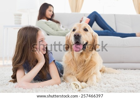 Happy girl looking at dog while lying on rug at home - stock photo