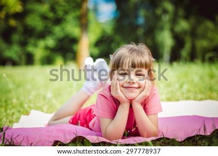 Happy girl lying in Park on blanket - stock photo