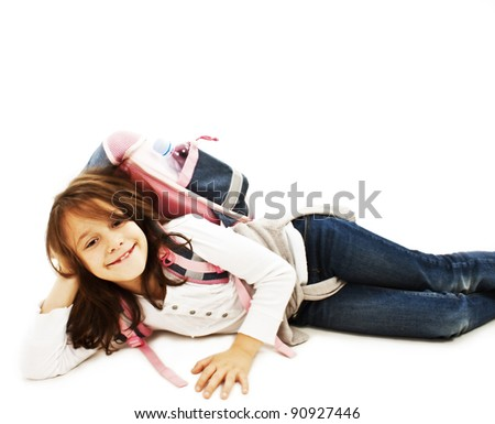 Happy girl lying on the floor with backpack, smiling. Isolated on white background - stock photo