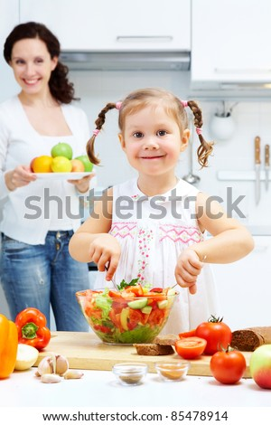 Happy girl mixing salad in bowl while woman holding plate full of fruits in the background - stock photo