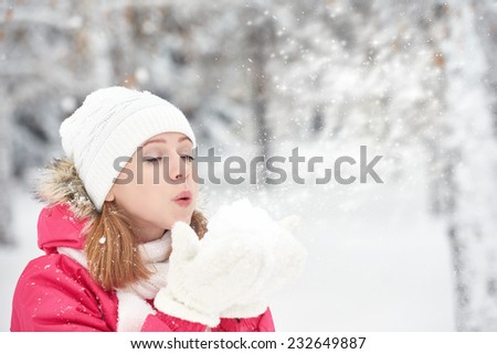 happy girl on a frosty winter walk on the street blows snow from hands - stock photo