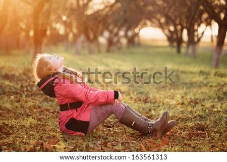 happy girl on grass in garden - stock photo