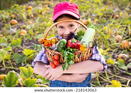 Happy girl on pumpkin's field with basket of vegetables - stock photo