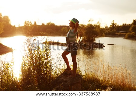 Happy girl on the bank of the river on a summer evening - stock photo