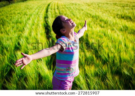 Happy girl on wheat field looking up - stock photo
