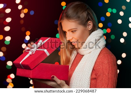 Happy girl opening Christmas box which is glowing inside. Christmas Gift - stock photo