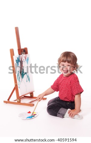 Happy girl painting on easel - stock photo