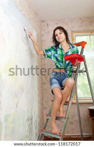 Happy girl paints wall with brush at home - stock photo
