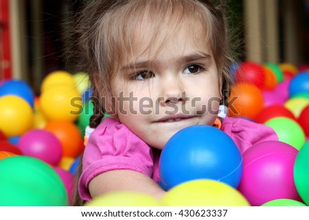 Happy girl playing and having fun at kindergarten with colorful balls, family weekend concept, happy birthday and merry party - stock photo