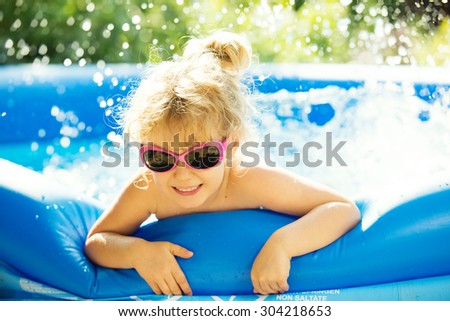 Happy girl playing in blue swimming pool. Summer holidays. - stock photo
