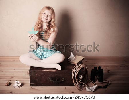 happy girl playing with toy sailing boat indoors - stock photo