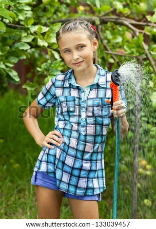 Happy girl pours water from hose, watering  flowers and grass - stock photo