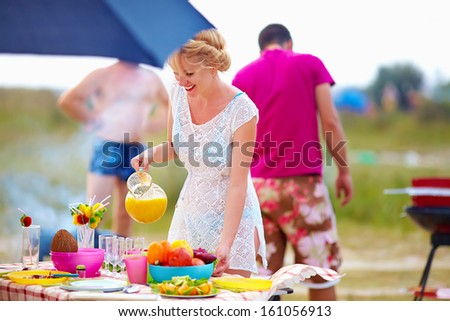 happy girl preparing food on picnic table - stock photo