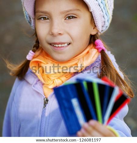 Happy girl-preschooler keeps bank credit card in city park. - stock photo
