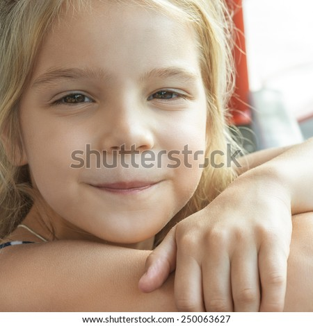 Happy girl-preschooler sitting on bench in city park. - stock photo