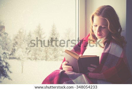 happy girl reading a book by the window in the winter - stock photo
