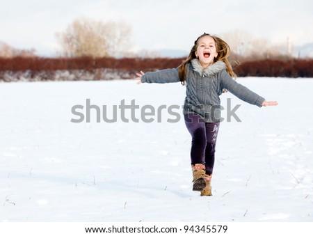 Happy girl running on snow in park - stock photo