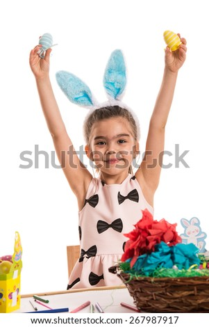 Happy girl showing Easter eggs and siiting at table  decorating   - stock photo
