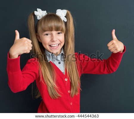 Happy girl showing thumbs up gesture in front of a big chalkboard. Back to school concept.  - stock photo