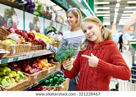 Happy girl shows broccoli in supermarket - stock photo