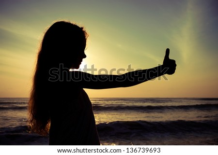 happy girl shows gesture cool on beach at dawn - stock photo
