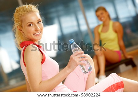 Happy girl sitting on mat with bottle of water with her friend on background - stock photo
