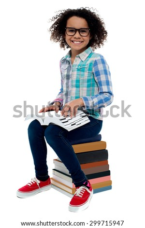 Happy girl sitting on stack of books over white - stock photo
