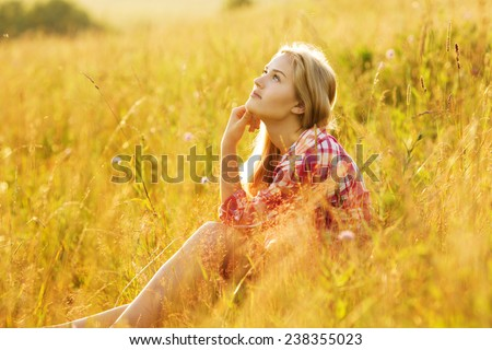 Happy girl sitting on the grass and dreaming - stock photo