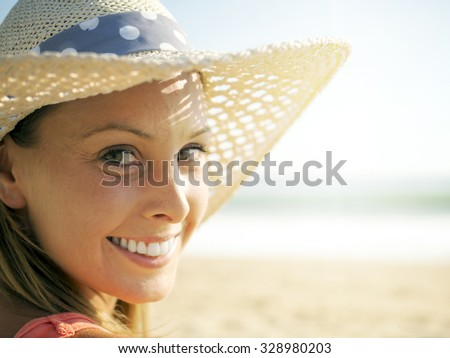 happy girl smiling portrait in the beach  wearing a picture hat with the sea and horizon in the background - stock photo