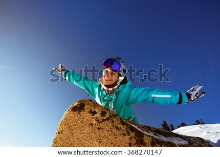 Happy girl snowboarder having fun lying on the rock and waving her arms like an airplane  - stock photo