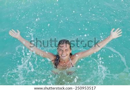 happy girl splashing in water - stock photo