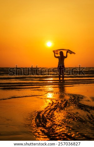 Happy girl standing on the beach in sunset - stock photo