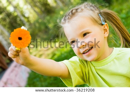 Happy girl stretching her arm with beautiful flower in it - stock photo