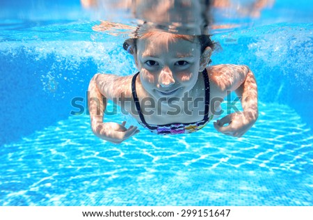 Happy girl swims in pool underwater, active kid swimming, playing and having fun, children water sport  - stock photo