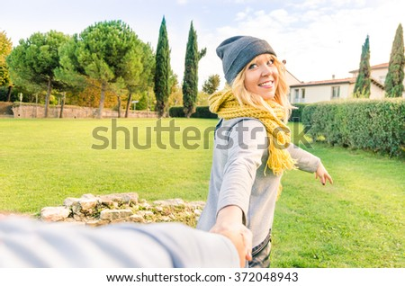 Happy girl take boyfriend hand to follow her in a magic love moment. Couple hand in hand ready for love adventure story. Happiness youth meeting outdoors. Love concept with girlfriend dating her guy - stock photo