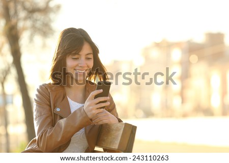 Happy girl using a smart phone in a city park sitting on a bench - stock photo