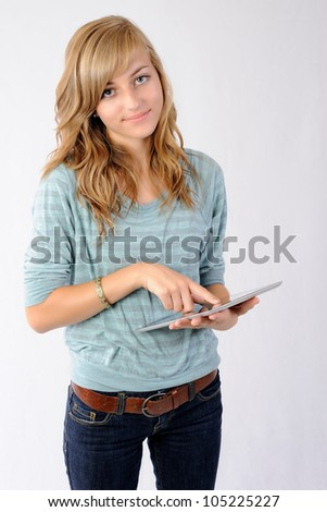 Happy Girl Using Tablet Computer. Teenage girl looking at the viewer as she uses a tablet computer. Note: Not Isolated. - stock photo
