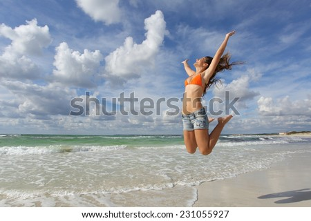 Happy girl wearing bikini jumping on the beach on holidays with a cloudy sky in the background - stock photo