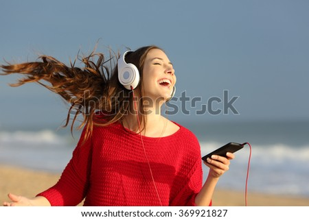 Happy girl wearing red colorful jersey dancing singing and listening music on line with headphones from a smart phone on the beach - stock photo