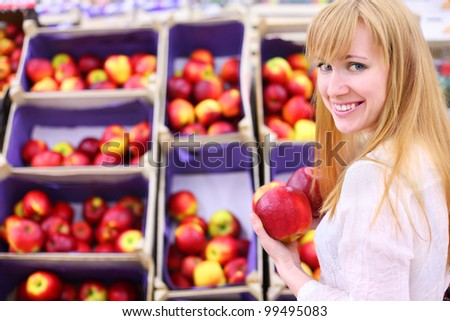 Happy girl wearing white shirt chooses apples in store; shallow depth of field - stock photo