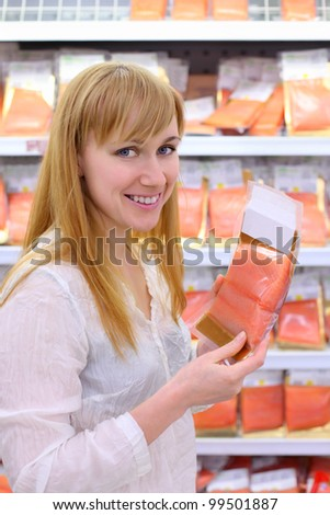 Happy girl wearing white shirt chooses salmon in store; shallow depth of field - stock photo