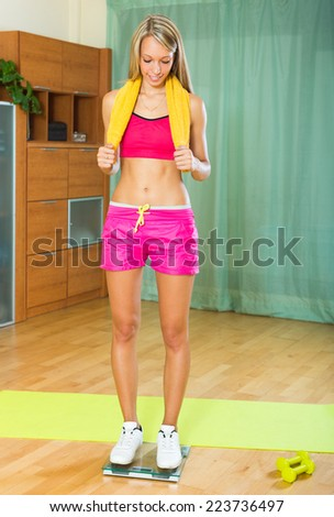 Happy girl weighing herself on the scale after training  - stock photo