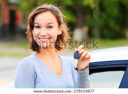 Happy girl with a car key smiling - stock photo