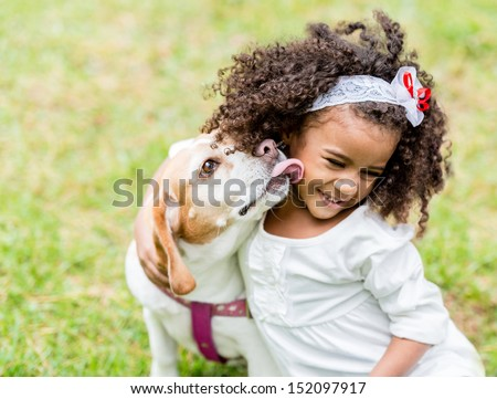 Happy girl with a dog licking her face  - stock photo