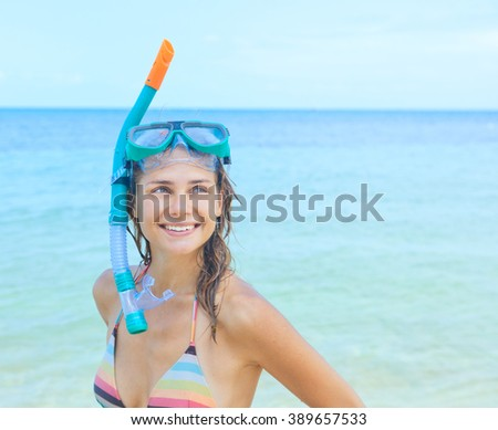 happy girl with a mask for snorkeling on a background of blue sea - stock photo