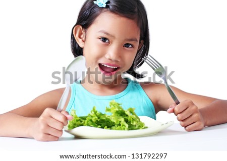 Happy girl with a plate of vegetable. - stock photo