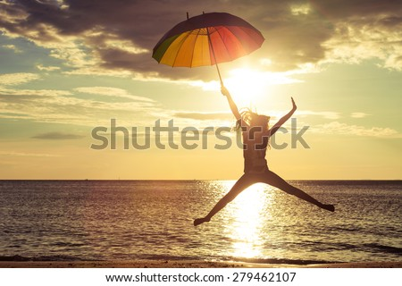 Happy girl with an umbrella jumping on the beach at the sunset time - stock photo