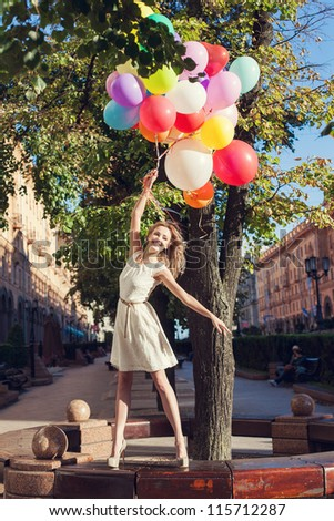 Happy girl with colorful latex balloons, urban scene, outdoors - stock photo