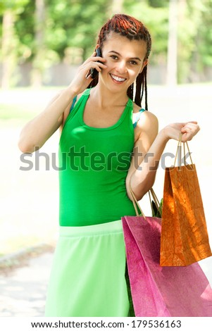 Happy girl with colorful shopping bags in the park - stock photo