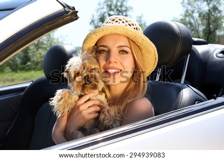 Happy girl with cut dog in cabriolet, outdoors - stock photo